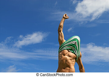 Happy winner with shirt on his head, on blue sky background