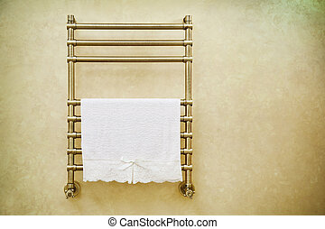 Modern heated towel rail on bathroom wall