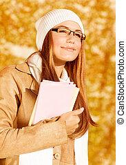 Happy student girl in autumn park