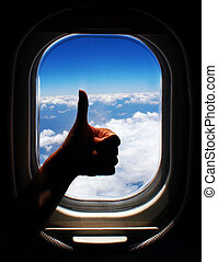 Airplane trip - Photo of person arm with thumb up in the...