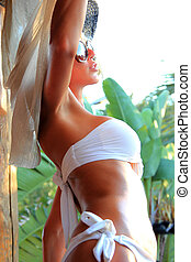 Young and sexy bikini model in tropical environment