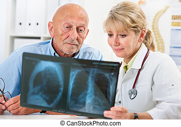 Medical exam - Doctor explaining x-ray results to senior...