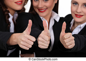 Three coworkers giving the thumb up