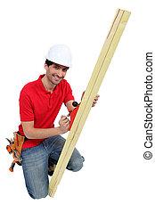 Man using wood plane whilst kneeling