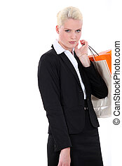 serious blonde woman in a black suit doing shopping