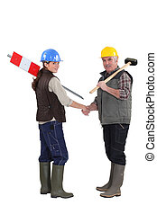 young female apprentice shaking hands with male instructor