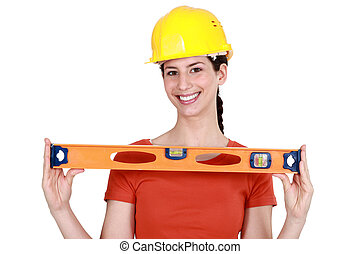 Brunette holding spirit-level