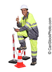 Man in high visibility overalls with a traffic cone and...