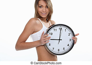 young sporty woman showing a clock