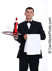 Waiter holding bottle of wine and glasses on tray
