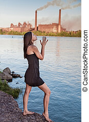 Young woman against of factory