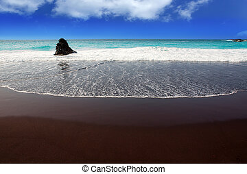 Beach el Bollullo black brown sand and aqua water near...