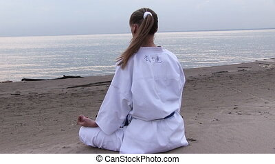 sunset meditation - young woman meditation on sunset beach