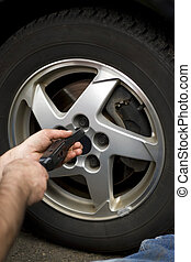 Wheel Mechanic - Close-up detail of a mechanic tightening or...