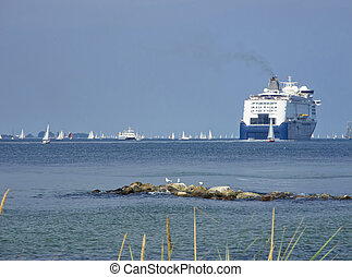 modern cruise ship and hundrets of sailing boats near by...
