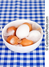 eggs and feathers in a bowl - brown and white eggs, feathers...