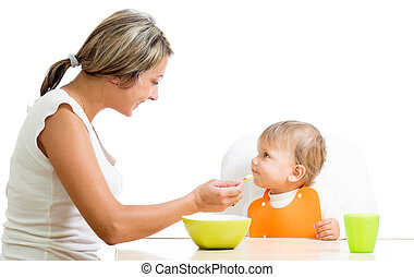 young mother spoon feeding her cute baby girl isolated on...