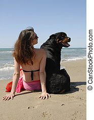 woman on the beach withe her rottweiler - young woman on the...