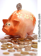 Piggy bank and lots of coins - Piggy bank standing in a pile...