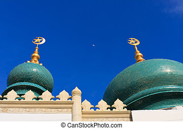 Moon between top of the tiled dome of the ancient mosque in...