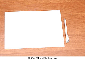 Blank sheet of paper with pen on wooden background