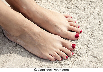 Toenails - Woman feet with red toenails on natural beach...