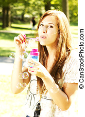 Girl having a pic nic in a park playing with bubbles - Girl...