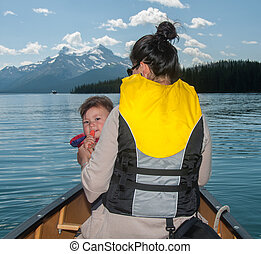 Mother and Baby Daughter In Canoe with mountains in the...
