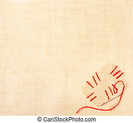 Canvas with stiched patch and needle over burlap background....