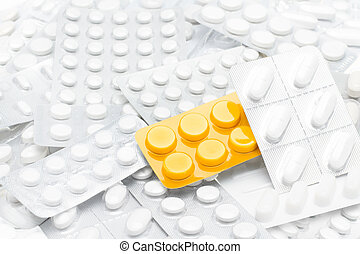 Pills in yellow package over white tablets background....