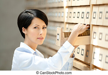 Pretty woman searches something in card catalog composed of...