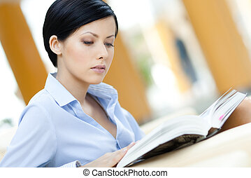 Business woman sits at the sofa reading interesting book at...