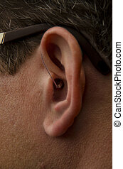 Hearing device - Young Caucasian male wearing/ using a...