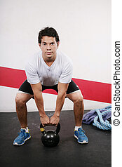 Young man Lifting Crossfit Kettle Bell