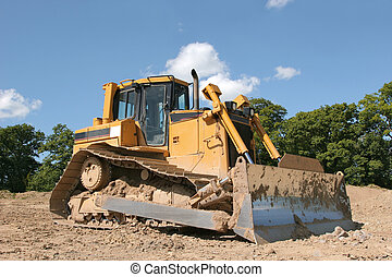 Bulldozer - Yellow bulldozer standing idle on rough earth...