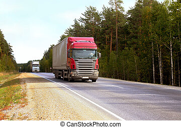 Two trailers go on highway along wood