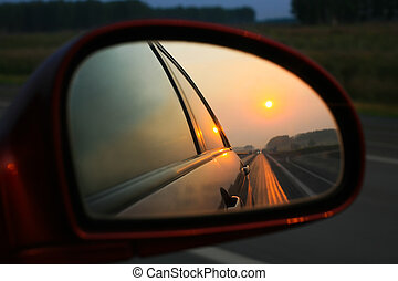 Sunset in mirror of car going on road