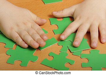 Puzzles and hands - Hands and green puzzle pieces on a...