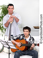 Man teaching teenage boy the guitar
