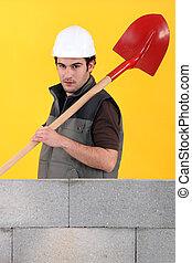 Mason stood by unfinished wall