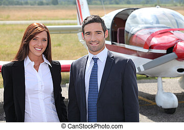 Man and woman in front of airplane