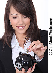 Young woman putting money into a piggy bank