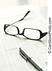 Financial tools - Glasses and pen on a stock market...