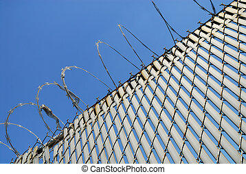 Fence with barbed wire against blue sky