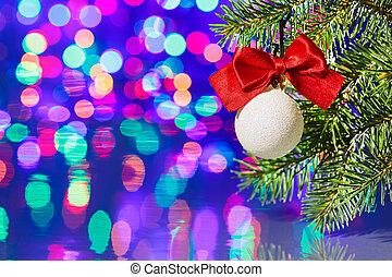 Christmas tree decoration ball with spruce branch on bokeh background
