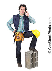 Portrait of a tradesman talking on his mobile phone and his foot propped up on a block