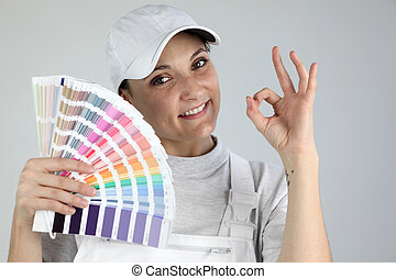 Painter giving the a-ok sign and holding a palette of colour...