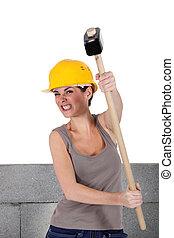 female bricklayer  holding hammer