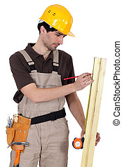 Tradesman measuring a plank of wood