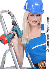 a blonde handywoman wearing an overall and posing with a...